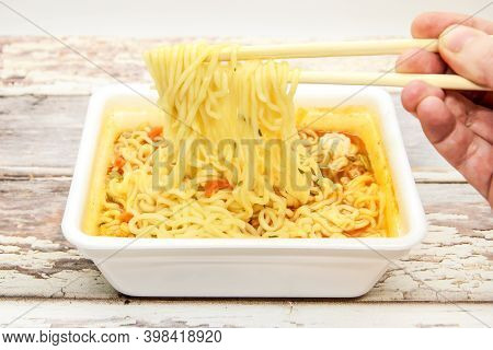 Instant Noodles With Vegetables And Spices With Red Pepper In Disposable Container With Wooden Chops