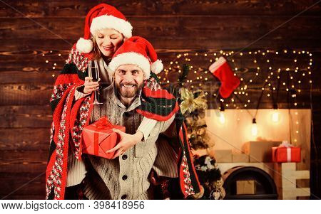 Man And Woman Santa Claus Hats Cheerful Celebrating New Year. Merry Christmas. Guy Piggybacking Girl