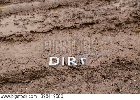 The Word Dirt Laid With Silver Letters On Wet Dirt Road Surface - Close-up With Selective Focus