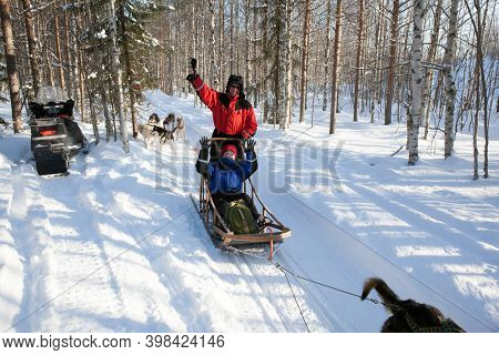 Exotic trip to the Arctic. Dog sled carries a sleigh with tourists. The sun is low on the horizon. Travel to Santa Claus. Short winter day in the Lapland