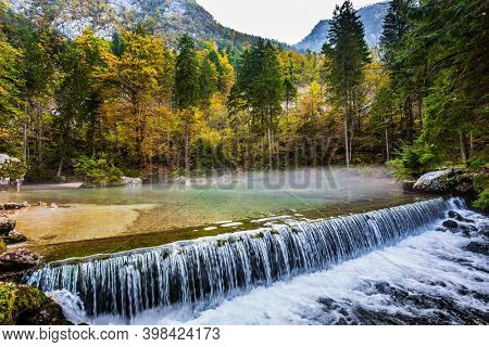 Artificial waterfall - dam. Autumn forest in a mountain valley. Picturesque shallow lake with glacial greenish water. Light fog rises above the water. Julian Alps, Slovenia