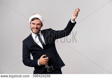 Young Handsome Caucasian Guy In Business Suit And Santa Hats Stands On White Background In Studio Pl