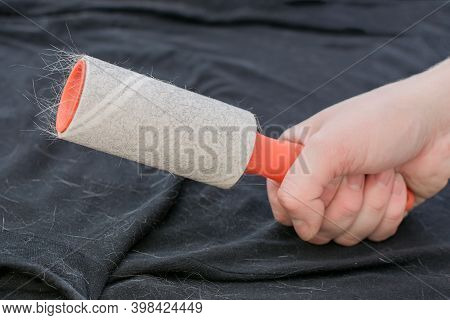 Velcro Roller With Orange Handle For Collecting Wool, Hair, Dust In A Persons Hand Against A Backgro