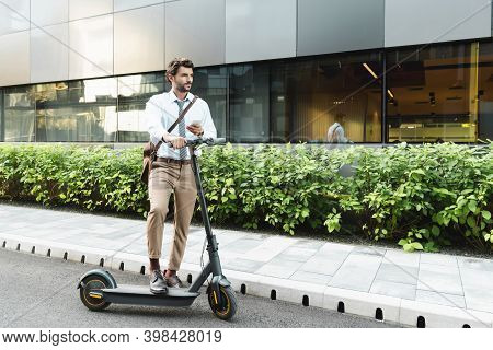 Full Length Of Businessman Holding Smartphone While Standing Near E-scooter, Plants And Building