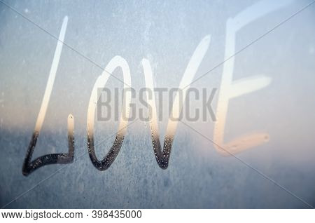 Love Drawn On Misted Window On The Background Of The City. Inscription Love With Finger On Misted Gl
