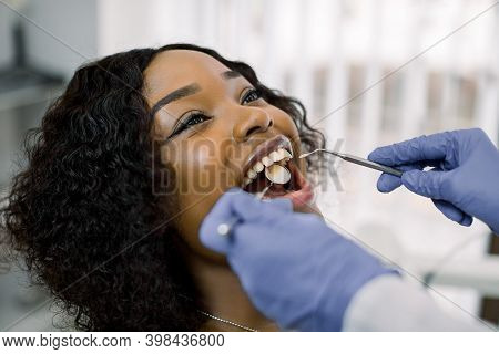 Close-up Portrait Of Pretty Young African Woman Patient Having Dental Examination And Treatment In D