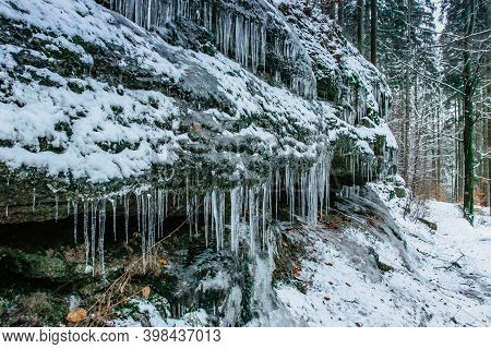 Icicles On Rock With Trees On The Background.snowy Winter Scenery.icicles In Colorful Nature Ice Bac