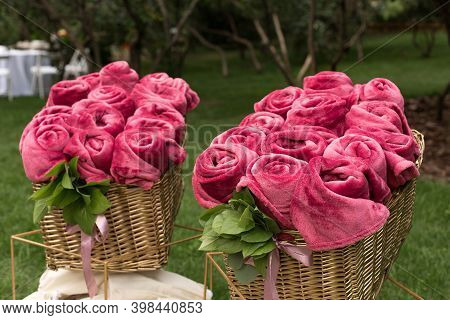 Warm Pink Blankets Rolled Up In The Form Of Roses In A Large Basket For Guests At An Outdoor Wedding