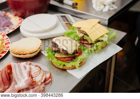 The Process Of Making A Burger In The Kitchen In A Diner, In The Foreground Is Bacon