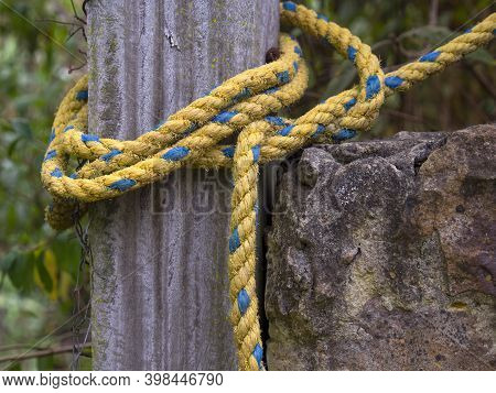 Close-up Photography Of A Yellow And Blue Nylon Rope Tied Up To A Wooden Post, Captured In A House N