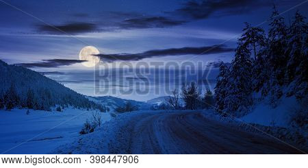 Road Through Mountain Landscape In Winter At Night. Spruce Forest Covered In Snow. Dramatic Sky With
