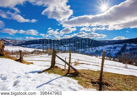 Mountainous Rural Landscape On A Sunny Winter Day. Fields And Trees On Rolling Hills Covered In Snow