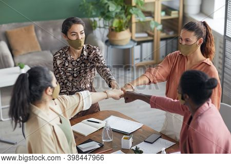 High Angle Portrait At Female Business Team Huddling And Bumping Fists While Celebrating Success At