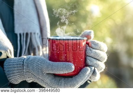 A Cup Of Hot Drink (tea, Coffee Or Mulled Wine) In Winter Nature. Female Hand With A Red Cup. Winter