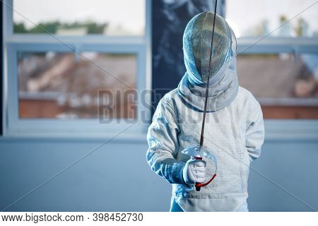 Child In A Fencing Costume And Mask, With A Sword, Fencing School
