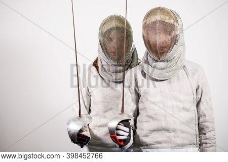 Teenage Girls In Fencing Costumes With Swords In Their Hands Isolated On White Studio Background. Yo