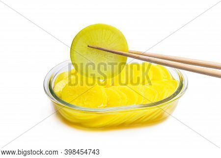 Marinated  Daikon Slice Picked Up With Chopsticks Isolated On White