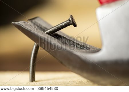 Pulling One Bent Nail Out Of A Wooden Board With A Hammer, Carpentry, Workshop