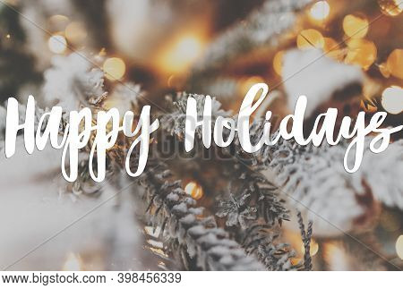 Happy Holidays Greeting Card. Happy Holidays Text Handwritten On Stylish Snowy Christmas Tree Branch