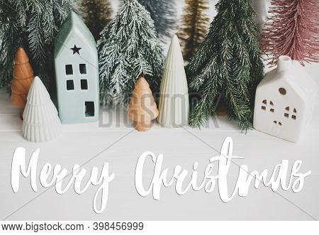 Merry Christmas Text Handwritten On Christmas Little Houses And Trees On White Background,  Winter H