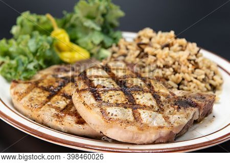 Fresh Off The Grill Pork Chops Served With All The Familiar Vegetable And Rice Sides.