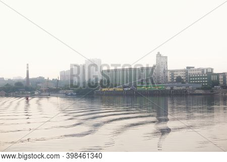 Urban Waterscape - Industrial City And Cargo Port In Fog On The Shore Behind A Wide Body Of Water