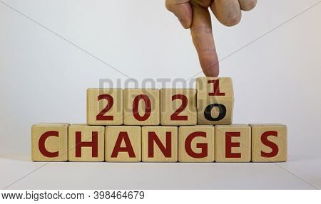 Business Concept Of 2021 New Year Changes. Male Hand Flips Wooden Cube And Changes The Inscription '