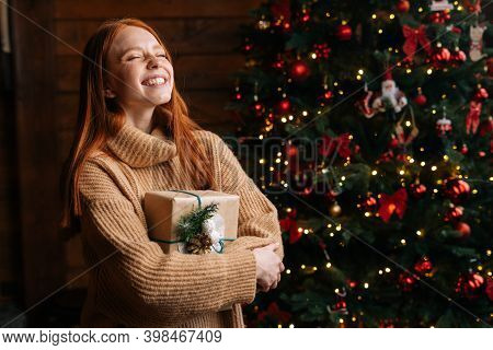 Close-up Portrait Of Excited Smiling Redhead Young Woman Holding Beautiful Christmas Gift Box On Bac