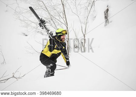 Happy Smiling Skier Walks In The Mountains In Deep Snow After Freeride Alpine Skiing With Ski On Sho