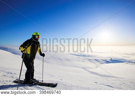 Male Freeride Skier In Northern Mountains In Lapland At Sunny Day Is Ready To Ride