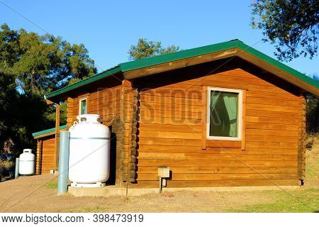 Modern Wooden Cabin Besides A Propane Tank For Heating Taken At A Campground Including Cottages With