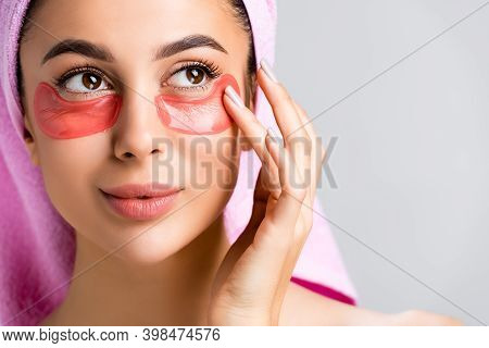 Beautiful Woman With Towel On Hair And Hydrogel Eye Patches On Face Isolated On Grey