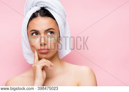 Pensive Beautiful Woman With Towel On Hair And Hydrogel Eye Patches On Face Isolated On Pink