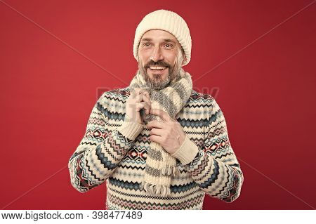 Cold Winter Conditions. Handsome Bearded Guy Wearing Hat And Scarf Red Background. Winter Sweater. K