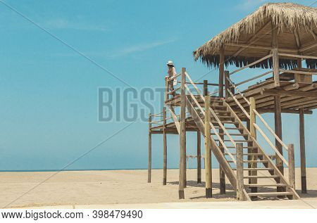 Beautiful Woman Latin Model Enjoys The Weather On The Beach While Posing Near A Lifeguard Station, C