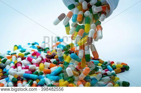 Pouring Multi-colored Capsule Pills From Plastic Drug Bottle. Antibiotic Drug Overuse Concept. Antib