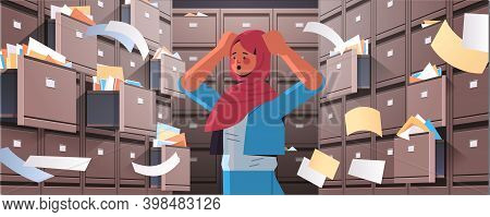 Overworked Arab Businesswoman Searching Documents In Filing Wall Cabinet With Open Drawers Data Arch
