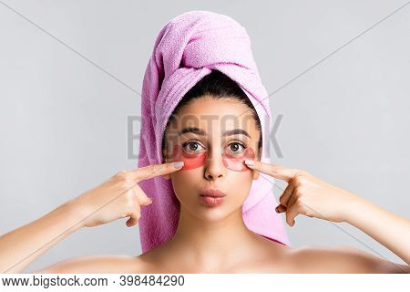 Beautiful Woman With Towel On Hair Pointing At Hydrogel Eye Patches On Face Isolated On Grey