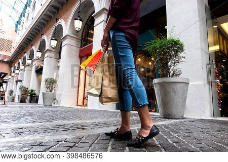 Woman Holding Shopping Bag While Walking On Vintage Street, Shopping Concept.
