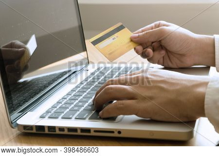 Man Holding Credit Card And Using Laptop For Shopping Online.