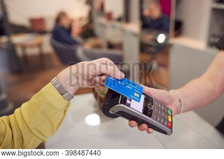 Close Up Of Senior Woman Making Contactless Payment To Stylist In Salon With Credit Card
