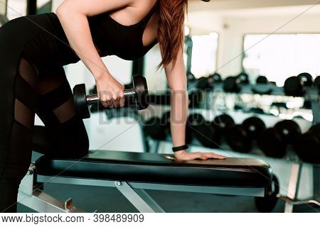 Fitness Girl Lifting Dumbbell In Fitness Gym. Fitness Workout And Muscle Concept.