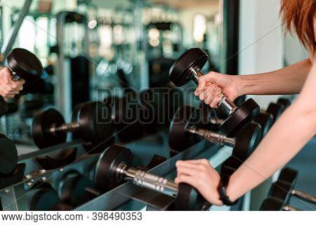 Women Hands Lifting Dumbbells Workouts With Dumbbells In A Gym. Sport Women At Fitness Gym.