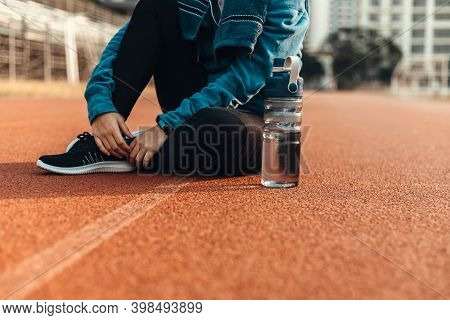 Woman Athlete Thirsty Takes A Break. She Sitting On The Track Race And Water Bottle Beside Her.