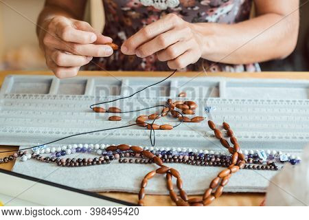 Close-up of woman making a necklace from gemstones putting them on string