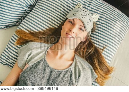 A Young Woman In Mask For Sleep, She Wakes Up From A Good Nights Sleep. Waking Up, Top View.