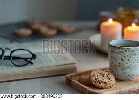 Reading Book On Cozy Winter Evening With Candles, Tea And Cookies. Side View