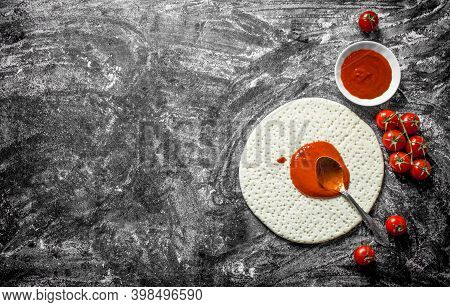 Preparation Pizza. Rolled Out Dough With Tomato Paste And Fresh Tomatoes. On Rustic Background