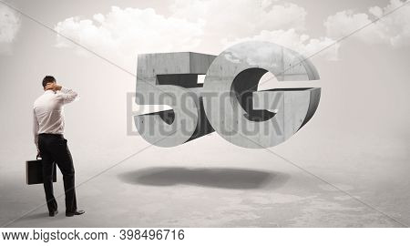 Rear view of a businessman standing in front of 5G abbreviation, modern technology concept