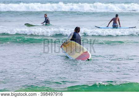 A Man With A Surfboard Enters The Water. Back View. Surfing Spot With Little Waves For Beginners. Sr